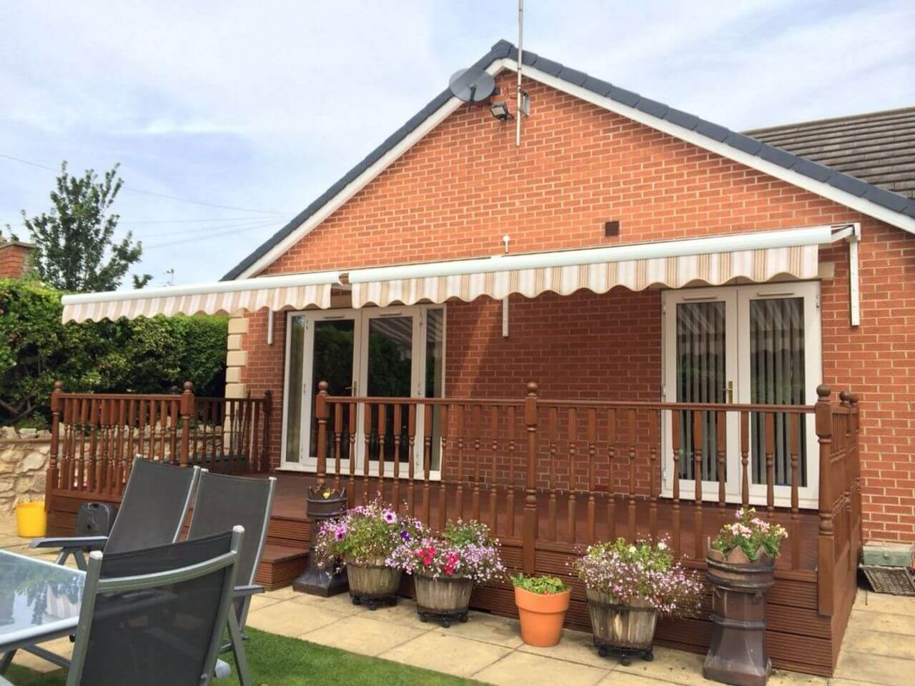 two harol electric patio awnings over decking on custom brackets fitted to a bungalow