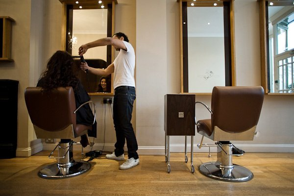 male stylist working on female client's hair