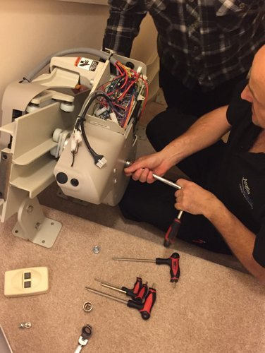 Professional doing the maintenance work on a Anglia Stairlifts Stairlift