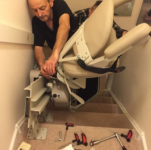 Anglia Stairlifts professional doing the maintenance work on the Stairlift in Peterborough
