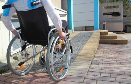 Individual on a wheelchair using assistive equipment offered by Anglia Stairlifts