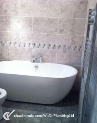A grey wet-room with white bidet and wall-mounted wooden washbasin stand