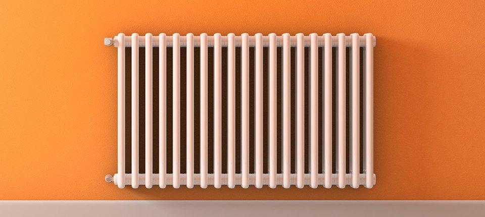 A white radiator on an orange wall