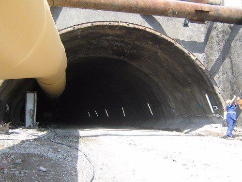 un tunnel e degli uomini al lavoro accanto