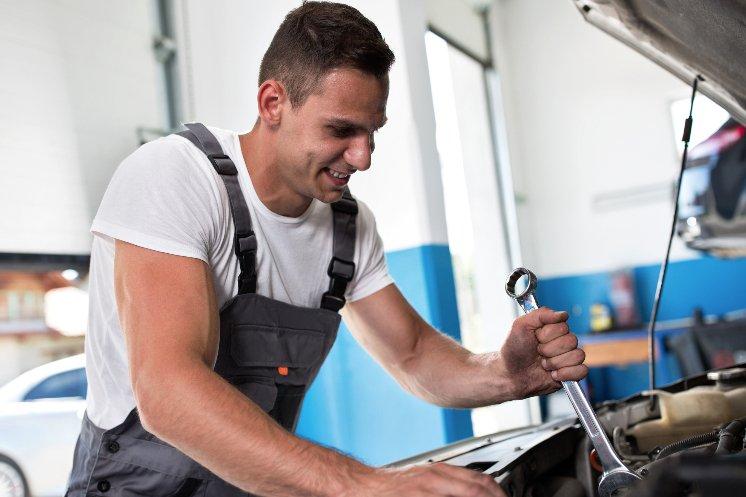 smiling man fixing engine