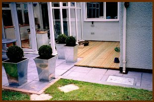 Garden with a decking, patio and grass area with plant pots on