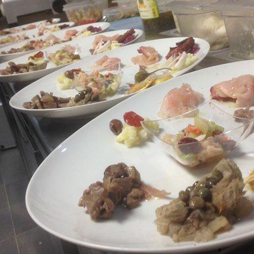 Dei piatti con carpaccio di  pesce e altri sottaceti