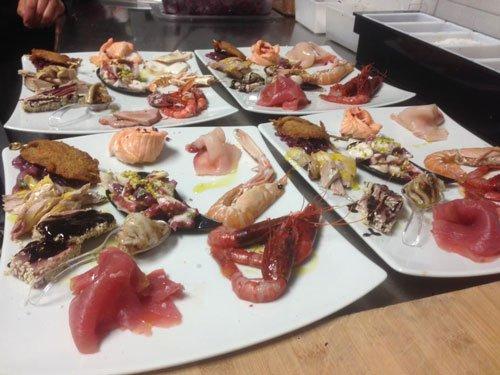 quattro piatti con antipasti a base di gamberi, scampi e carpaccio di pesce