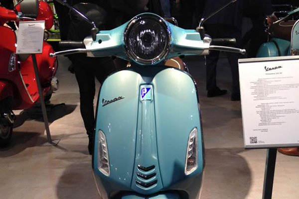 uno scooter Vespa di color azzurro visto da davanti
