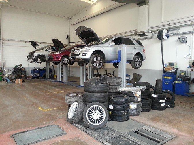 vista interna di autofficina con pila di gomme e macchine durante riparazione