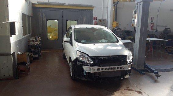 vista frontale di una macchina bianca in una officina durante riparazione