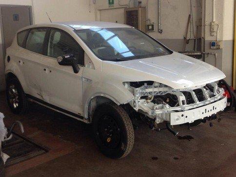vista laterale di una macchina bianca in una officina durante riparazione