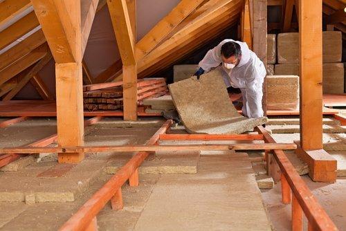 uomo che installa strato di isolamento termico sotto tetto con pannelli