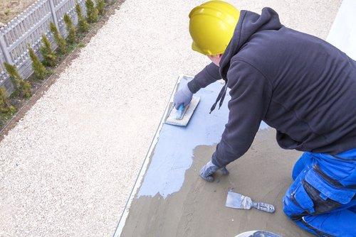 operaio mentre lavora in cantiere per impermeabilizzazione del cemento
