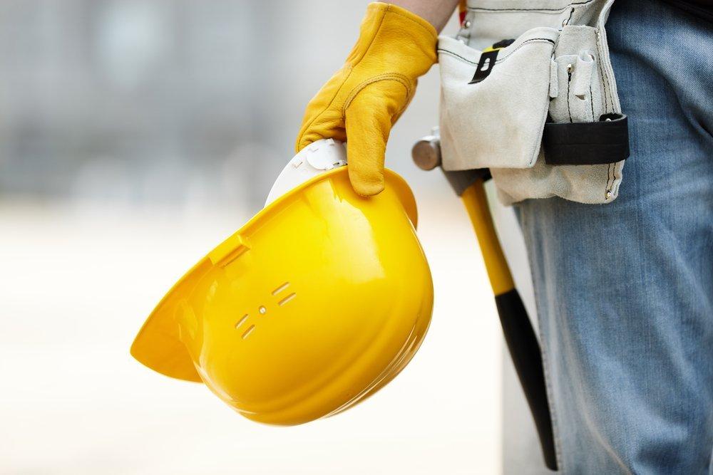 operaio con elmetto e strumenti costruzione
