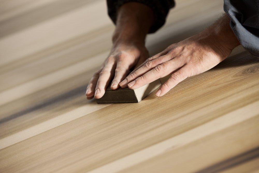 carpentiere durante levigatura e finitura di superficie del legno