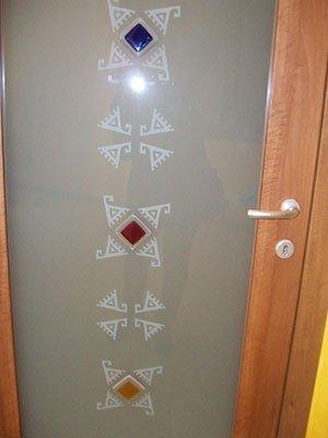 una porta con un pannello di vetro con dei disegni colorati