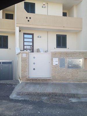 uno stabile con un cancello di color bianco e una porta con pannelli di vetro
