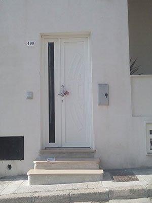 una porta d'ingresso di color bianco con un pannello di vetro sul lato