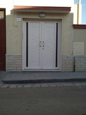 una porta da esterno con due ante di legno di color bianco
