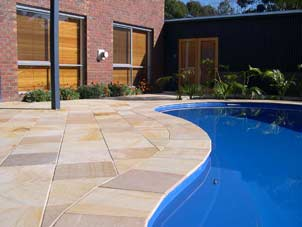 stone tiling by deep blue pool