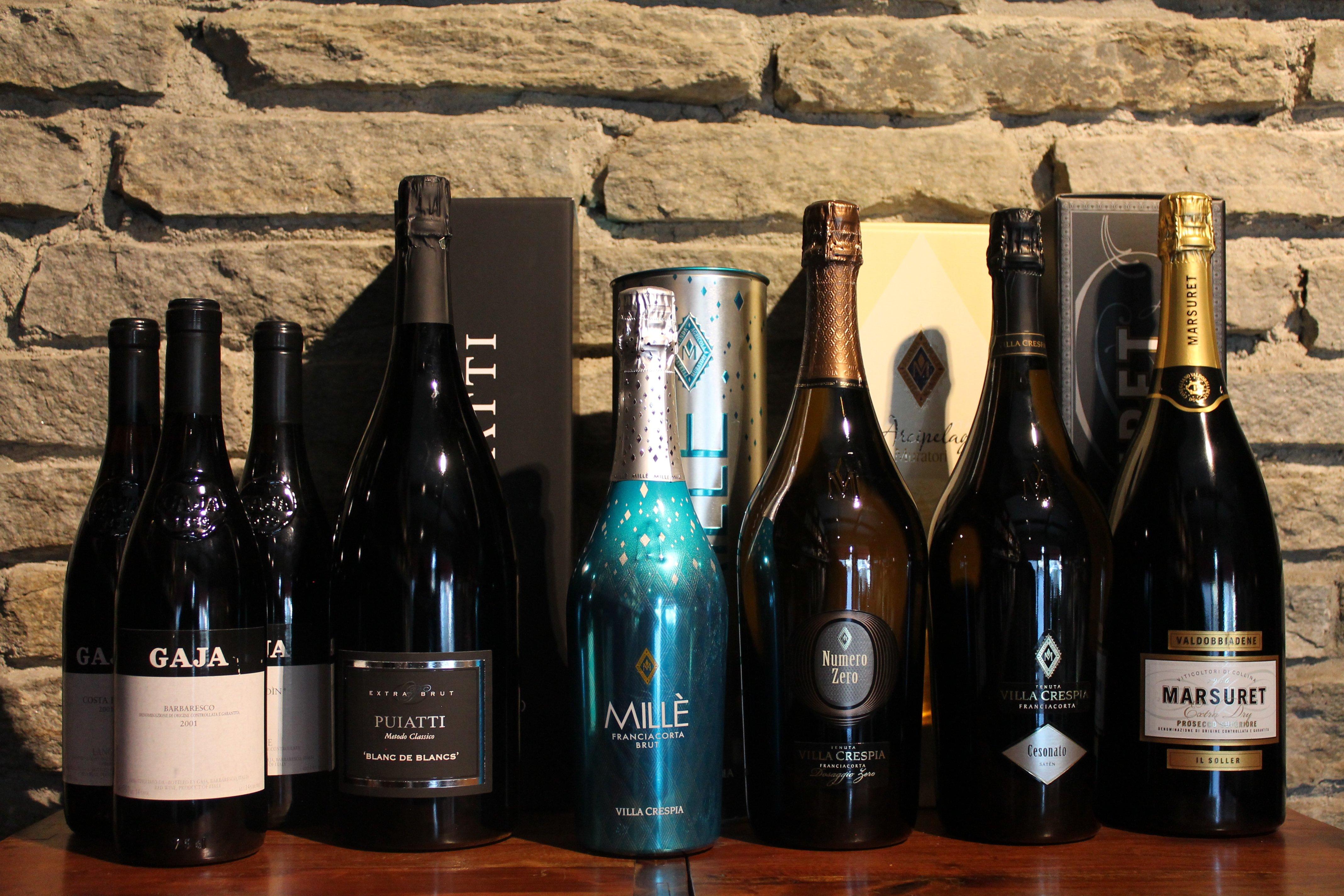 bottiglie di vino su scaffale di legno davanti a muro in pietra vista