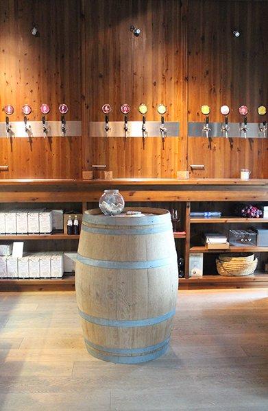 un barile e dietro una serie di rubinetti di vino alla spina su una parete di legno e sotto un mobile