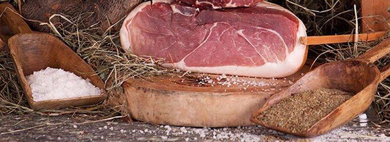 un trancio di prosciutto su un tagliere e accanto due palette di legno con del sale da una parte e degli aromi dall'altra