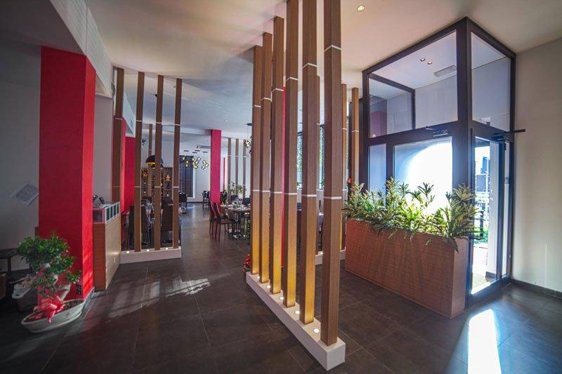 Delle colonne di legno e le piante in un vaso all'interno di un ristorante