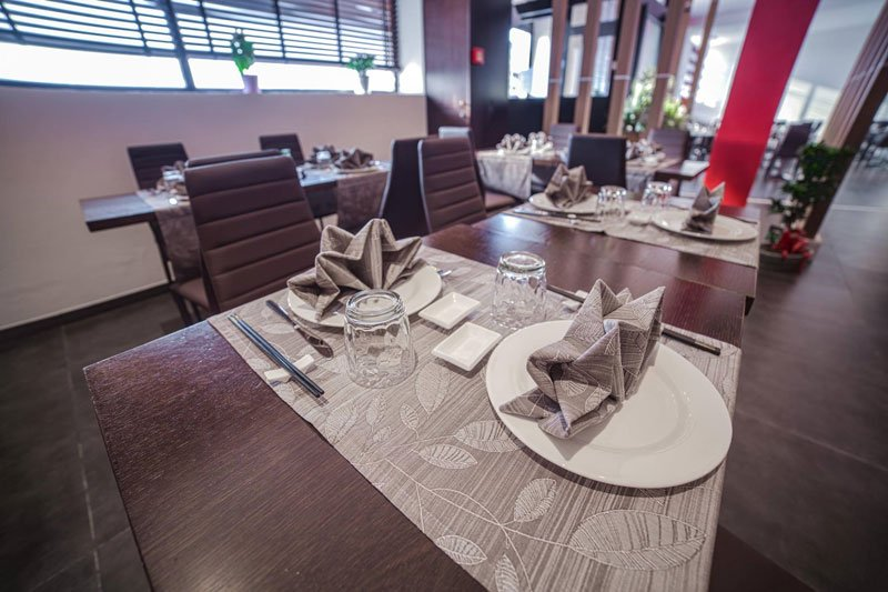 Vista ravvicinata dei piatti bianchi con tovagliolo di color grigio e delle bacchette nere