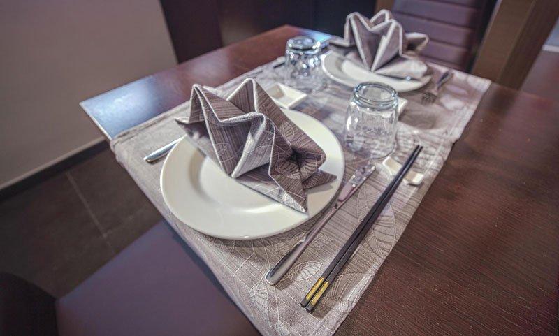 Vista ravvicinata di un tavolo apparecchiato con dei piatti bianchi, posate, bicchieri e delle bacchette