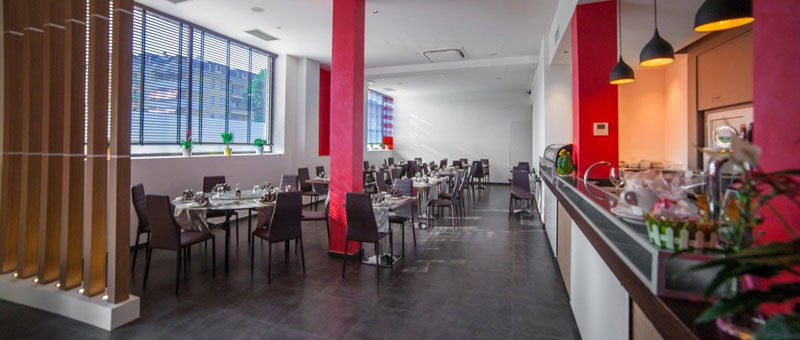 Dei tavoli apparecchiati sulla sinistra e sulla destra un bancone da bar