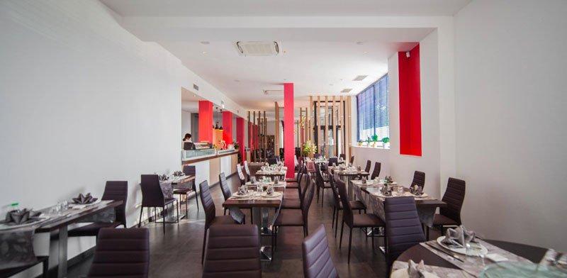 una sala lunga con dei tavoli apparecchiati