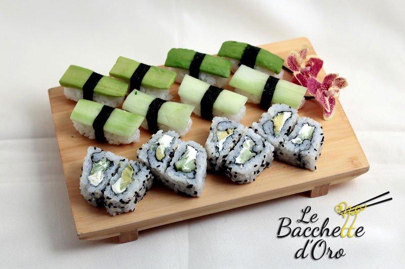 Un tagliere con del sushi e delle verdure
