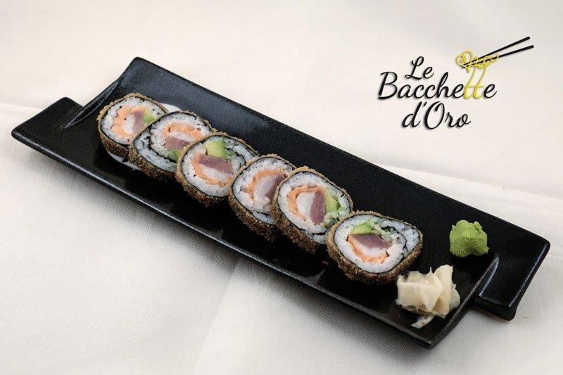 Un vassoio nero con del sushi, salsa wasabi e fette di zenzero
