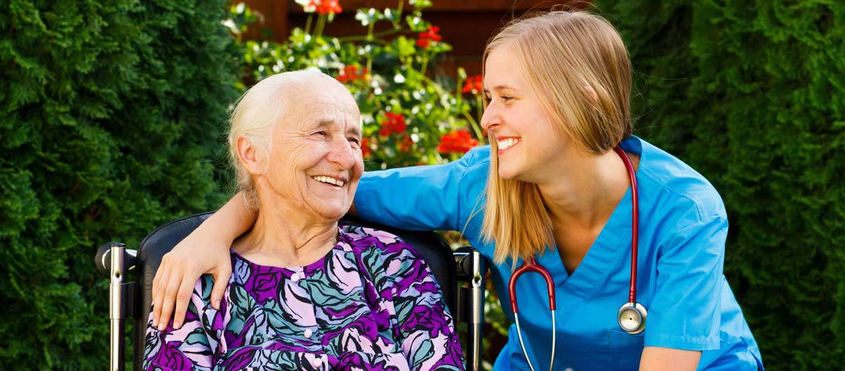 Supporting young doctor with elderly patient at nursing home