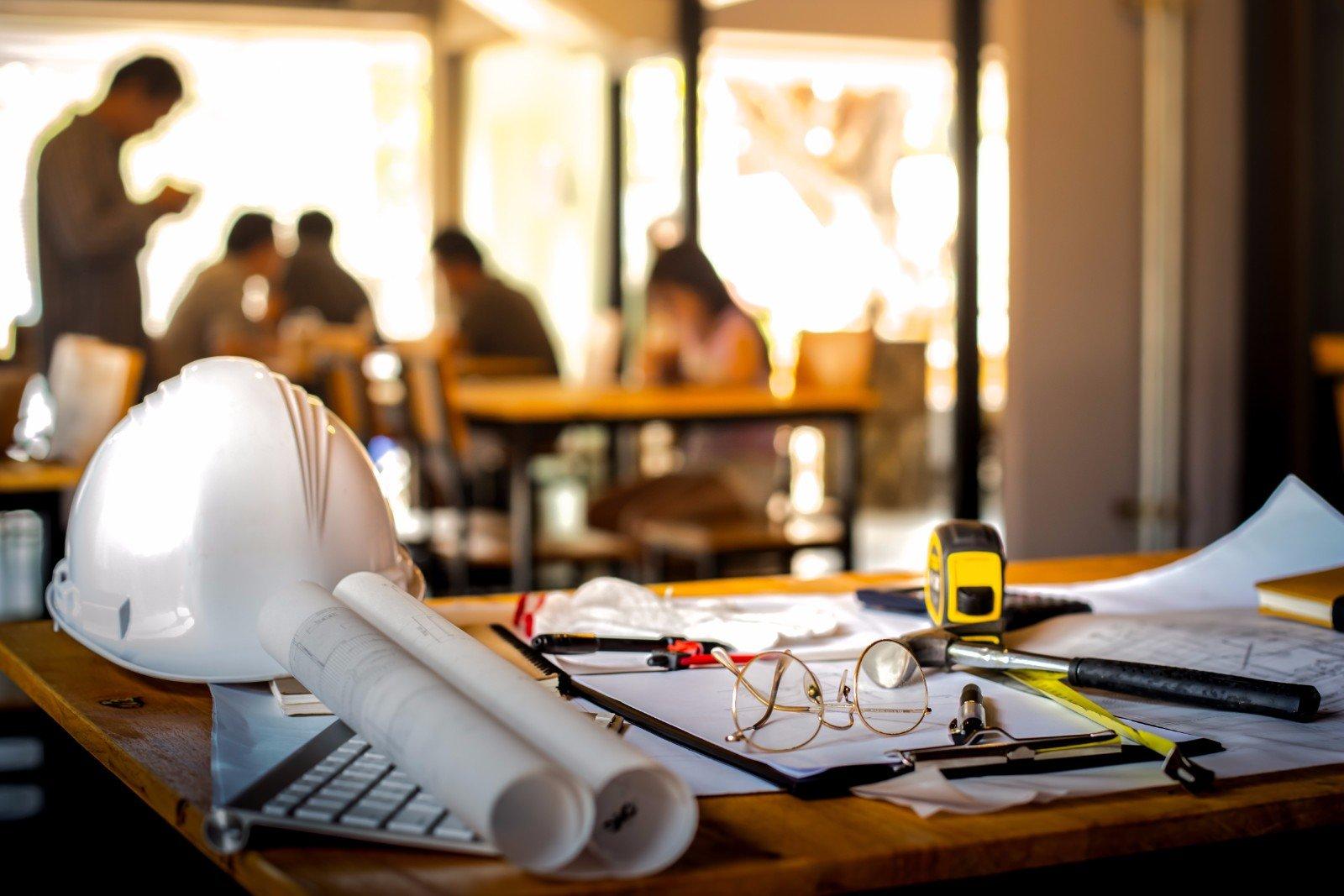 Su una tavola diversi oggetti connessi con la costruzione includendo un elmetto,pianti e di occhiali per l'architetto