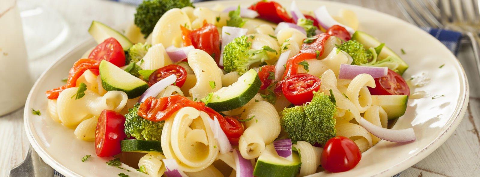 Un piatto con insalata di pasta con verdure