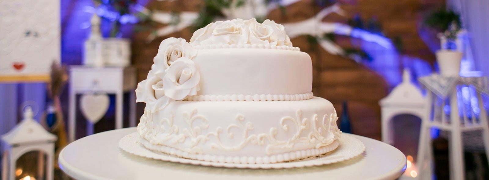 Una torta nuziale con delle decorazione con dei fiori bianchi