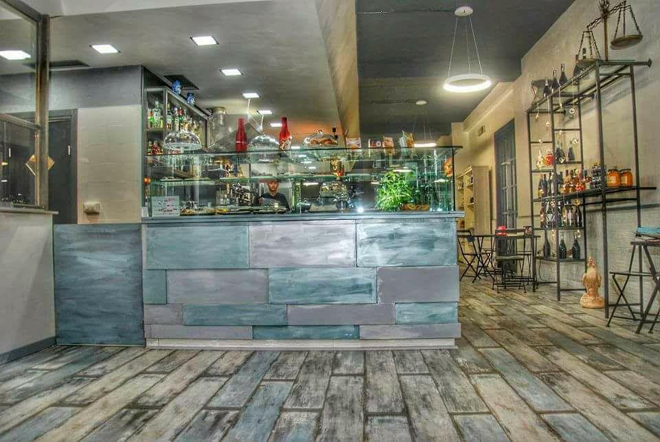 interno del ristorante con di fronte un bancone con una vetrina con sopra degli oggetti e sulla destra degli scaffali in ferro con altri oggetti