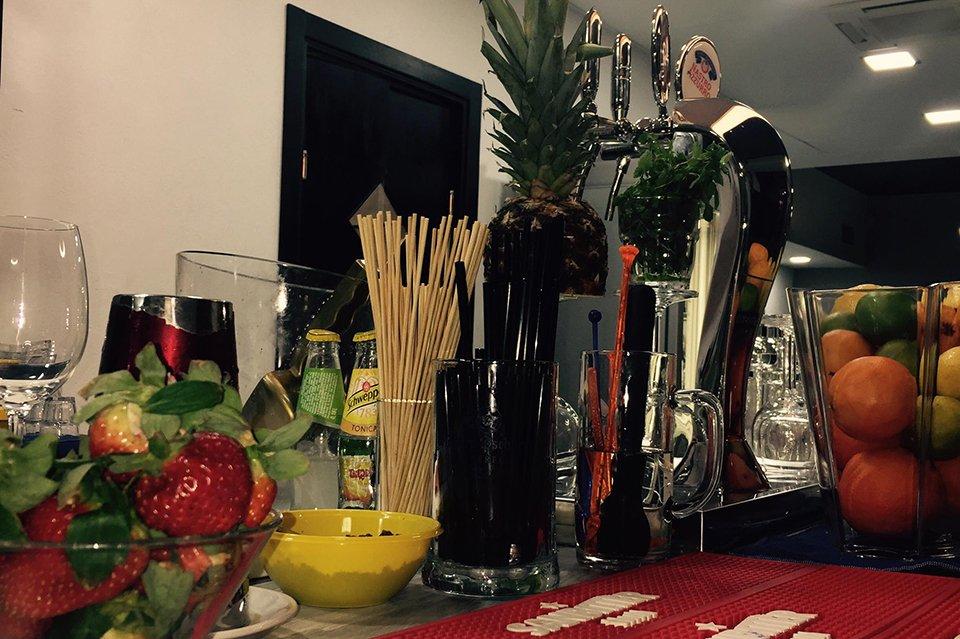 vista ravvicinata di una bacinella con delle fragole,dei bicchieri, un boccale, i rubinetti per la birra alla spina,un ananas e altra frutta sulla destra