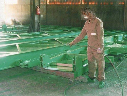 operaio durante una fase di sabbiatura e verniciatura