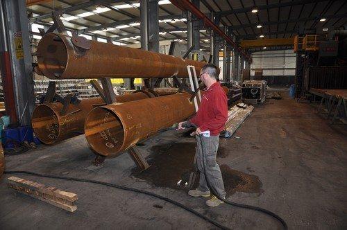 operaio lavora su dei tubi di acciaio  di una  granigliatrice