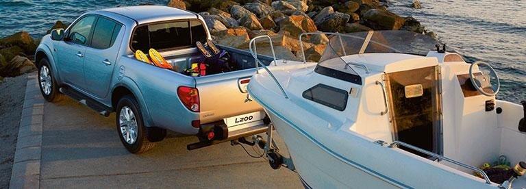 un pick up grigio Mitsubishi L200 che traina una barca