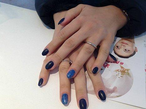 due mani con le unghie con dello smalto viola e blu