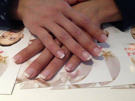 delle mani con dello smalto trasparente