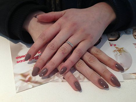 delle mani con uno smalto beige