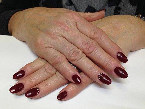 delle mani con uno smalto rosa scuro