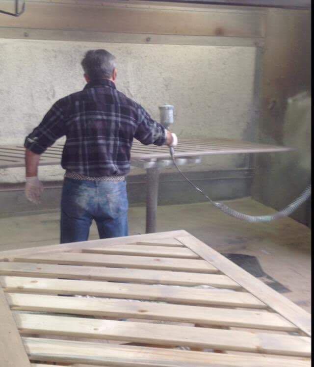 Operaio vernicia una griglia in legno
