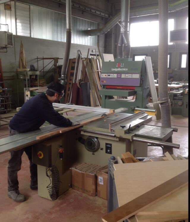Operaio lavora sul taglio laser di un elemento d'arredo in legno